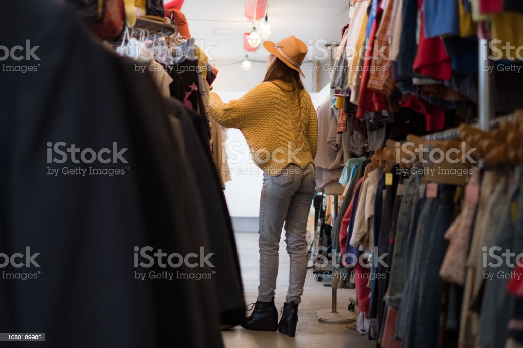 A woman enjoying casual clothes shopping in a clothing store.