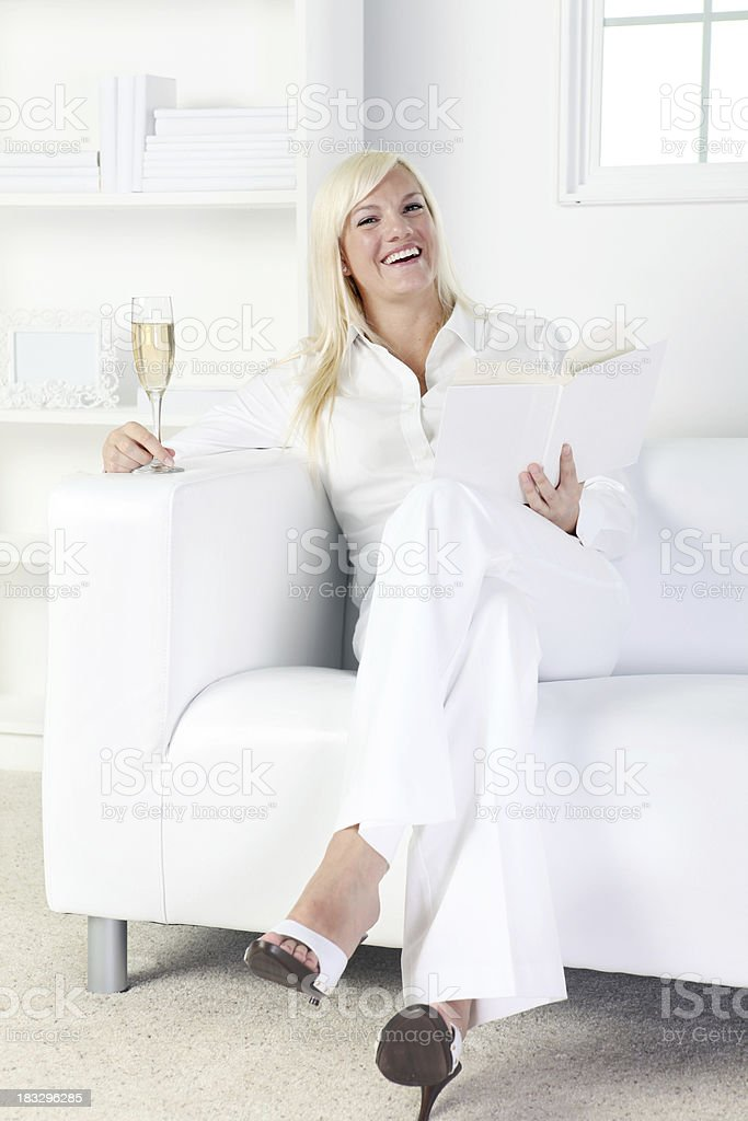 Woman enjoying champagne and reading book royalty-free stock photo
