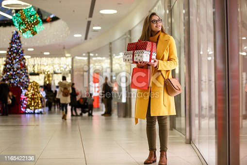 Young woman is holding gift boxes and shopping bags and looking at shop windows at the mall. The shopping mall has a large and beautiful Christmas tree.