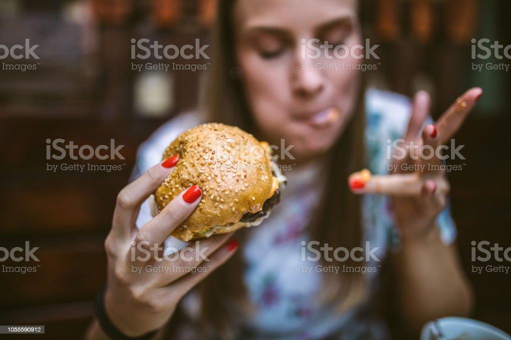Woman Enjoying Delicious Burger stock photo