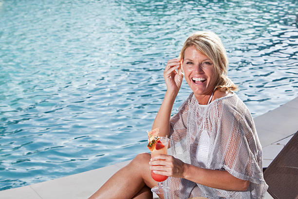 Woman enjoying drink by pool Mature woman (40s) sitting by swimming pool, enjoying tropical drink. middle aged women in bikinis stock pictures, royalty-free photos & images