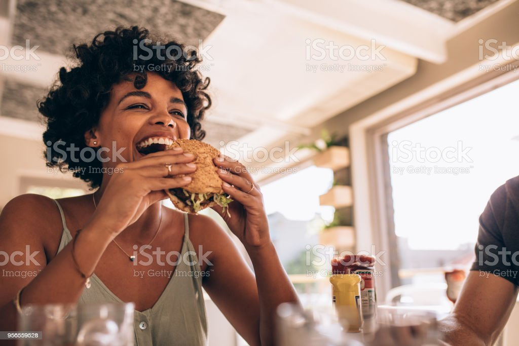 Woman enjoying eating burger at restaurant stock photo