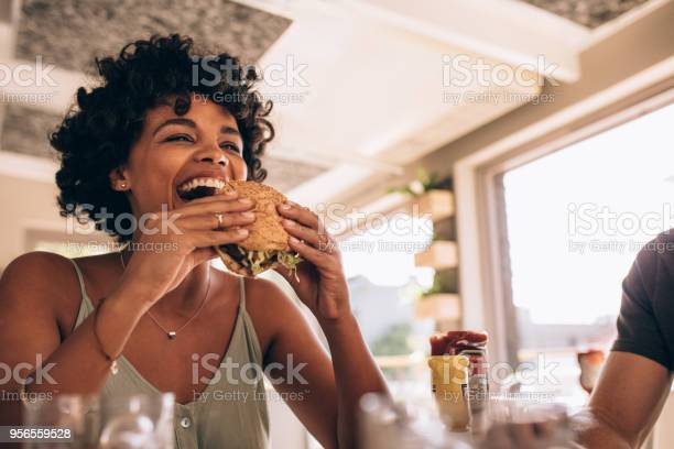 African woman eating stack burger at restaurant with friends. Happy young woman having junk food at cafe with friends.