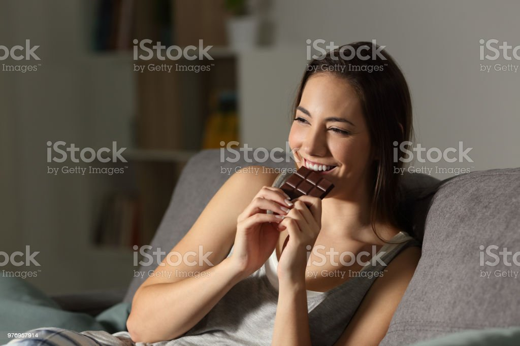 Woman enjoying eating chocolate in the night stock photo