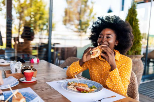 Femme appréciant le sandwich de manger au restaurant - Photo