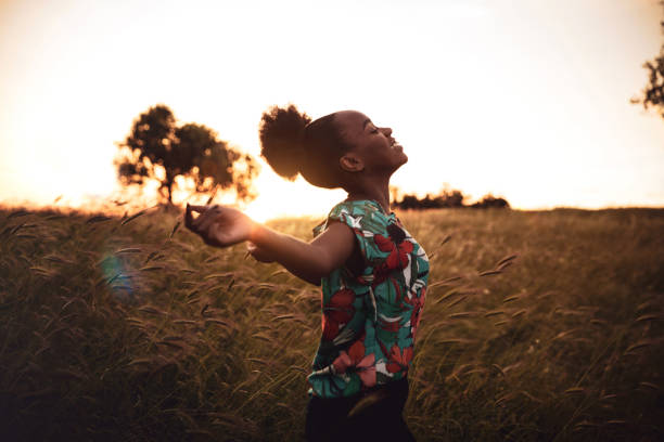 Woman enjoying freedom in a beautiful sunset in countryside stock photo