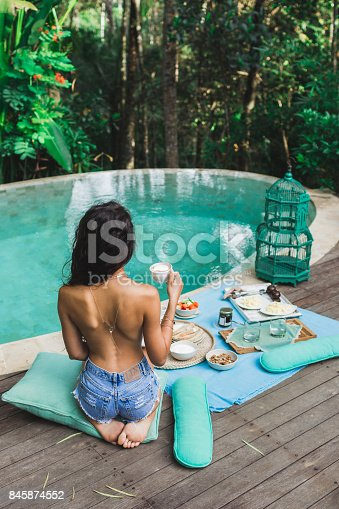 istock Woman enjoying fresh breakfast on private villa with swimming pool. Glamping tent style. Jeans short and tanned body 845874552