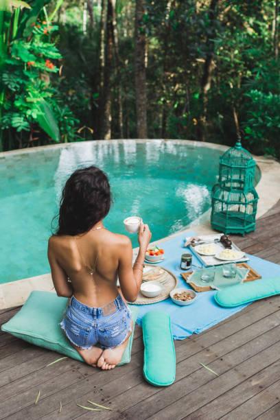 frau frisches zubereitetes frühstück auf private villa mit pool zu genießen. glamping-zelt-stil. jeans kurz und gebräunte körper - badewannenkissen stock-fotos und bilder