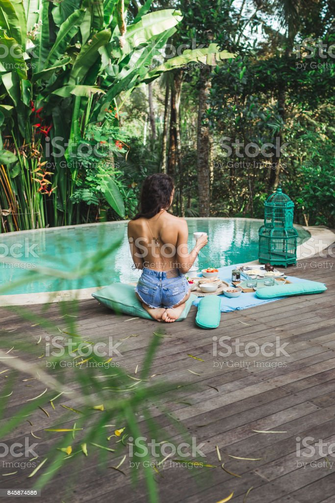 Woman enjoying fresh breakfast on private villa with swimming pool. Glamping tent style. Jeans short and tanned body stock photo