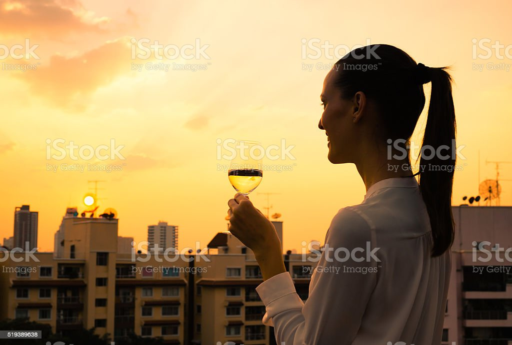 Woman enjoying glass of wine in the city stock photo