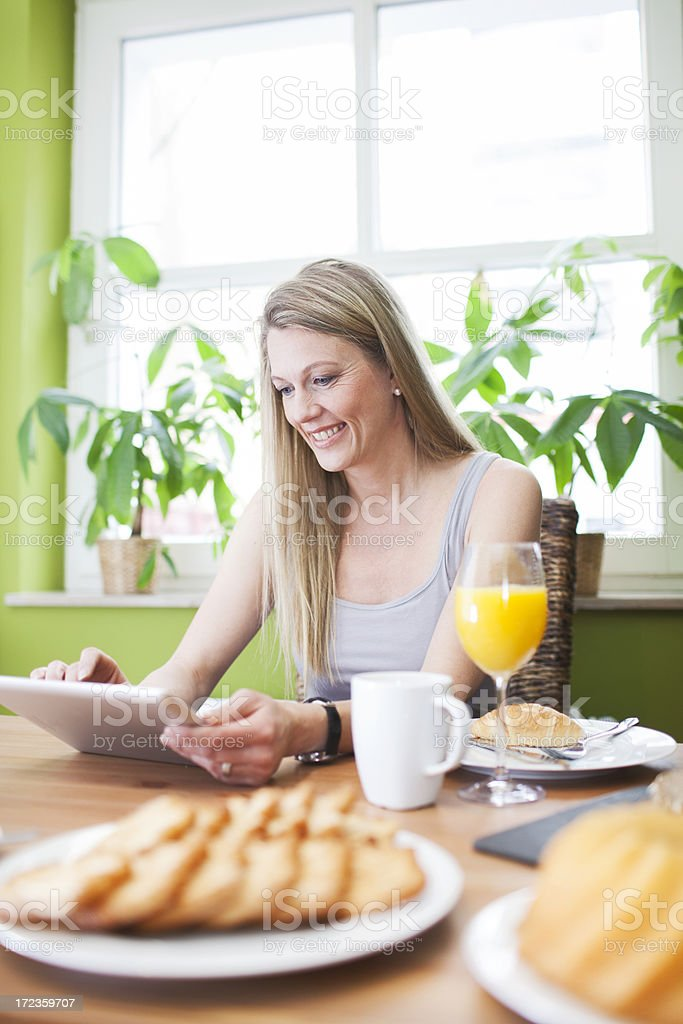 Woman enjoying her digital tablet during breakfast. royalty-free stock photo