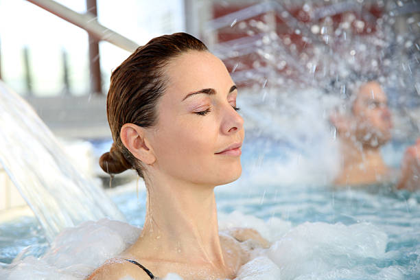 Woman enjoying hydrojet shower stock photo