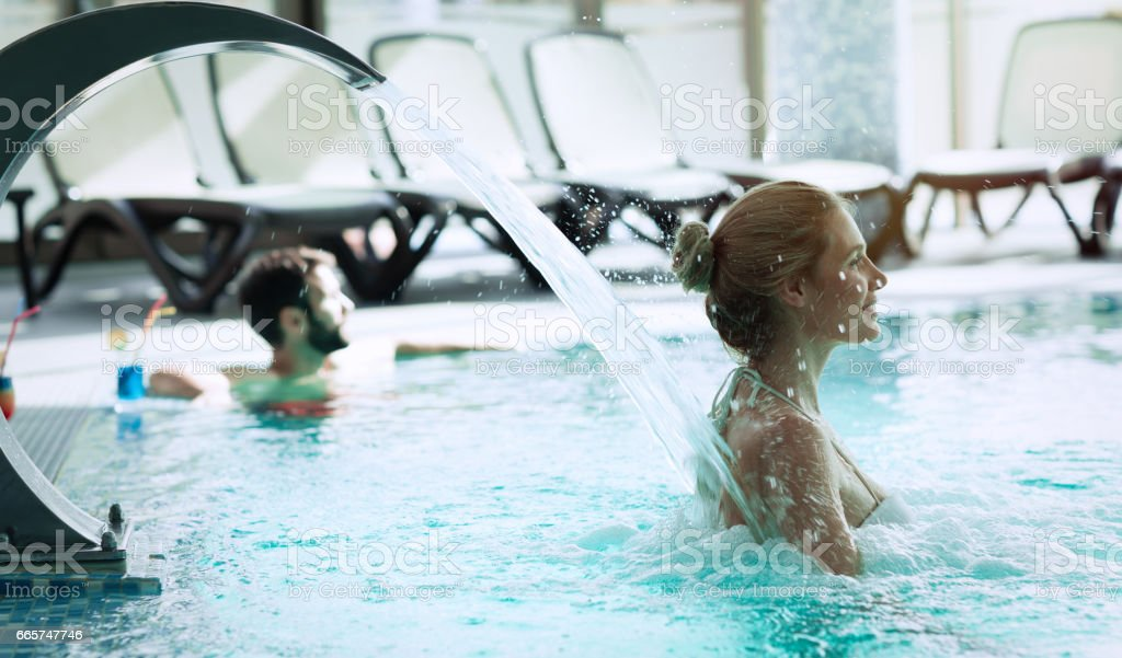Woman enjoying hydrotherapy and water stream in spa pool stock photo