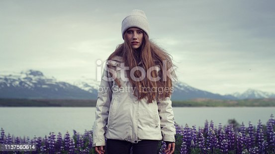 Young woman posing on a meadow. Blooming lupines and mountain ridge in background
