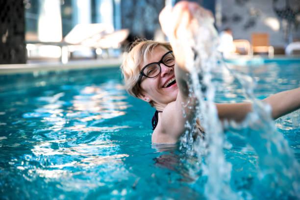 Woman enjoying in a pool stock photo