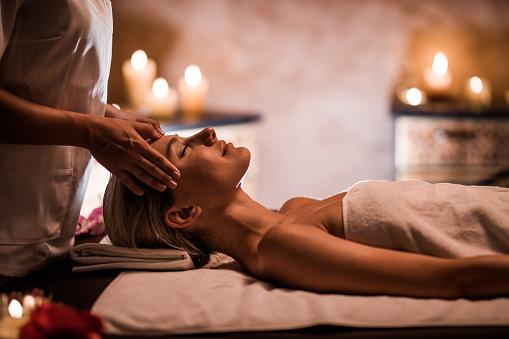 Young woman having facial massage at the health spa.