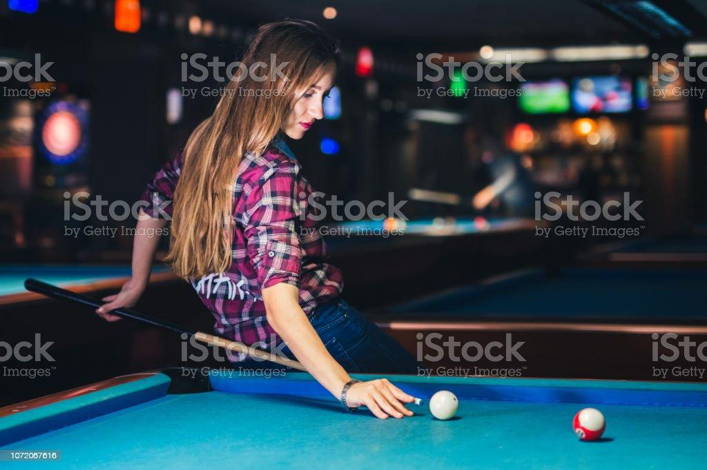 Young caucasian woman enjoying in night life and billiard game.