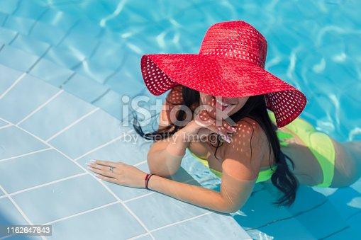 Beautiful young woman wearing bikini in swimming pool with sun hat