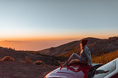 Landscape view on the roadside above the clouds with woman enjoying beautiful sunset, sitting on the convertible sports car