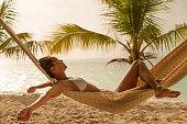 young woman in white bikini enjoying little rain while relaxing in a hammock at a Caribbean beach