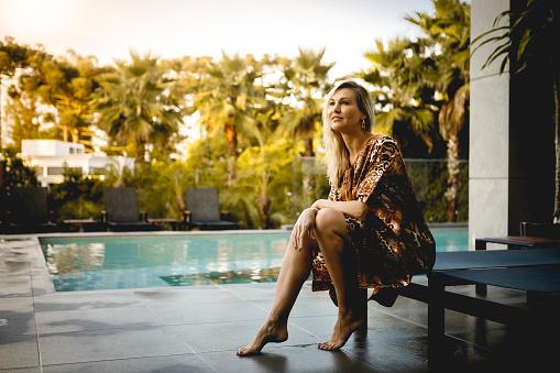 woman enjoying luxury pool on sunny day