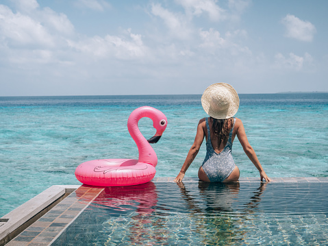 Woman enjoying tropical vacations from the edge of an infinity pool in private over water villa. People travel luxury holidays