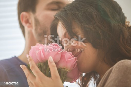 Mid adult man and woman with bouquet of pink roses sharing romantic moments.