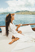 Woman enjoying morning coffee on boat in private cruise tour. Bed on board. Travel and freedom lifestyle. Mountain view of Komodo national park on horizon.
