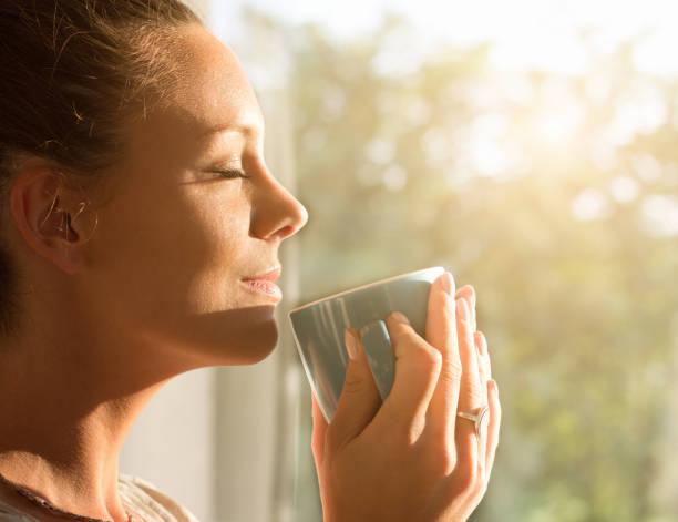 mujer disfrutando de un café por la mañana - café bebida fotografías e imágenes de stock