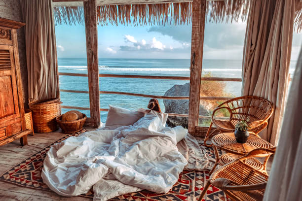 Woman enjoying morning vacations on tropical beach bungalow looking ocean view Relaxing holiday at Uluwatu Bali ,Indonesia Woman enjoying morning vacations on tropical beach bungalow looking ocean view Relaxing holiday at Uluwatu Bali ,Indonesia beach hut stock pictures, royalty-free photos & images