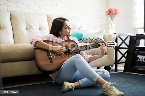 istock Woman enjoying music by playing the guitar 839969478