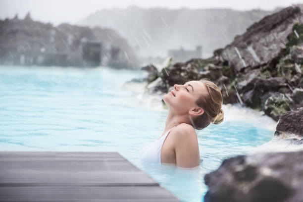 Woman enjoying natural spa Woman enjoying natural spa, Blue Lagoon is a geothermal spa in southwestern Iceland, is located in a lava field near Grindavk on the Reykjanes Peninsula spa stock pictures, royalty-free photos & images