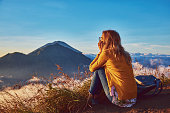 Woman enjoying nice landscape and sunrise from a top of mountain Batur, Bali, Indonesia.