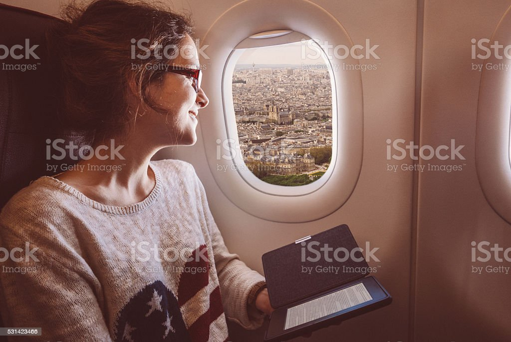 Woman enjoying Notre dame de Paris from the airplane window stock photo