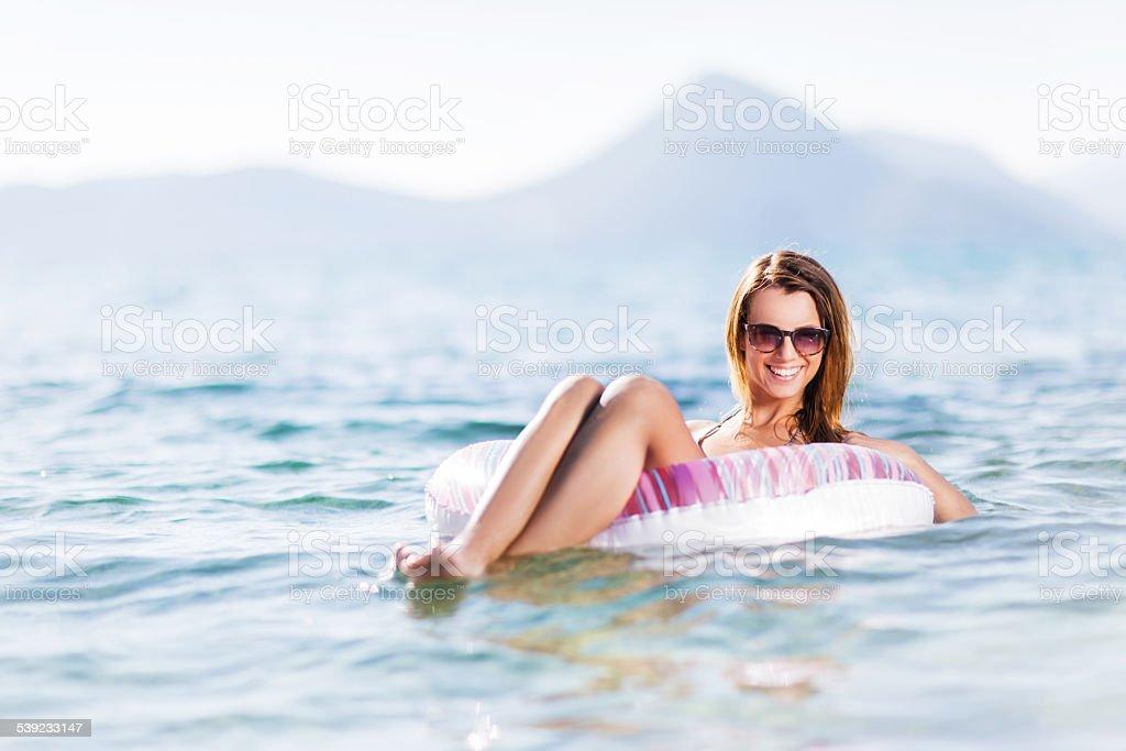 Mujer disfrutando en colchonetas inflables tubo. foto de stock libre de derechos