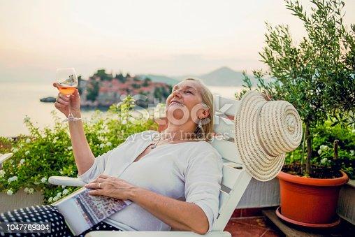 istock woman enjoying on the balcony having a glass of wine 1047769304
