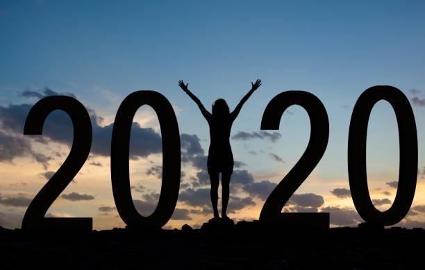 Woman enjoying on the hill while celebrating new year 2020 stock photo