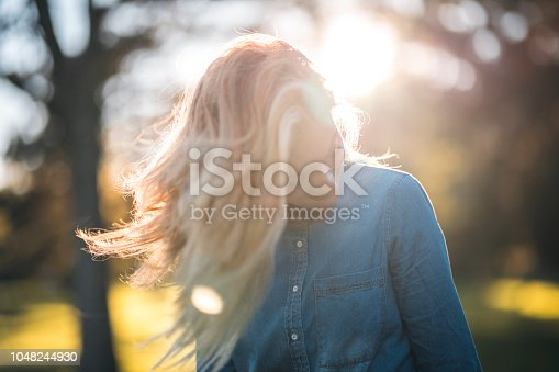 Woman enjoying in a park on a sunny summer day. She is spinning around and having fun. Sun is shining from back.