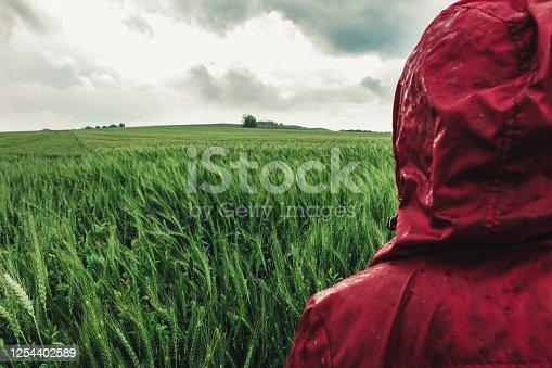 Woman enjoying rainy grey springtime day outdoors. Soft daylight