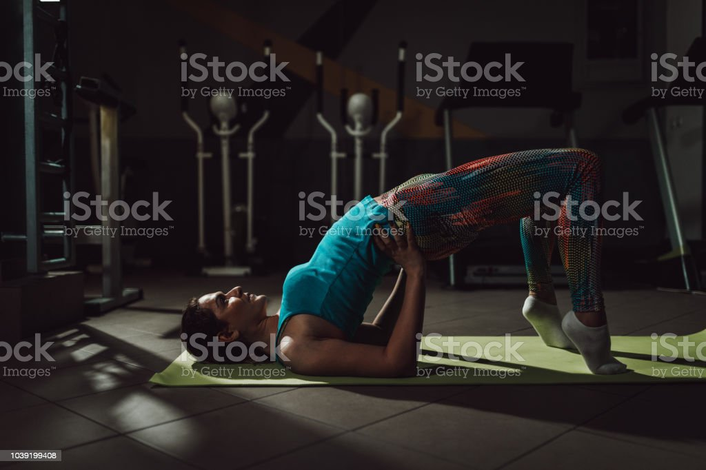 Woman enjoying relaxing yoga exercise in the gym