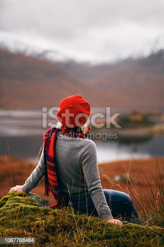 Senior woman wearing a tartan scarf above the shores of Loch Quoich in the Knoydart region of Scotland.
