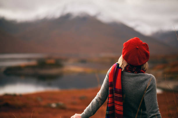 Woman enjoying retirement in Scotland Highlands Senior woman wearing a tartan scarf above the shores of Loch Quoich in the Knoydart region of Scotland. beret stock pictures, royalty-free photos & images