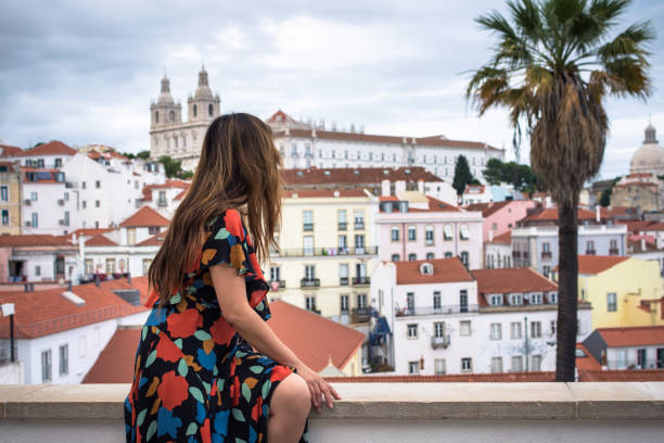 Woman enjoying rooftop view of Alfama District - Lisbon, Portugal stock photo
