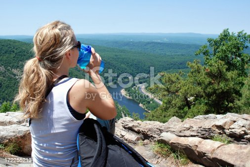 Young woman taking a rest during a hike and enjoying the scenery.