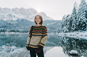 Young Caucasian woman enjoying scenic view of Eibsee lake in Alps in winter