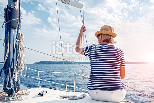 879618770 istock photo Woman Enjoying Sea on Sailboat 1127077889
