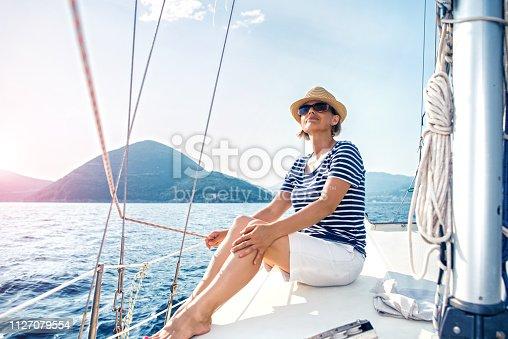 879618770 istock photo Woman Enjoying Sea on Sailboat 1127079554