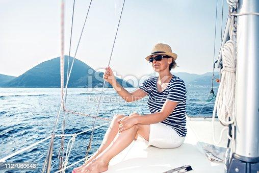 879618770 istock photo Woman Enjoying Sea on Sailboat 1127080646