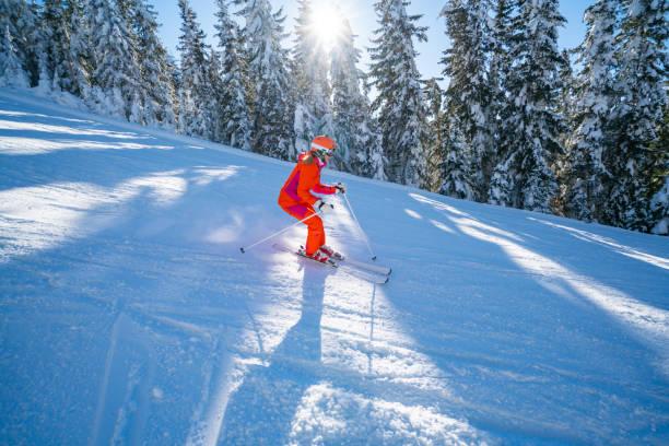 woman enjoying skiing on sunny winter day stock photo