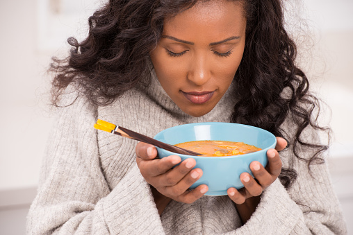 Beautiful young woman eating tom Yum soup, closing her eyes enjoying aroma of delicious soup.